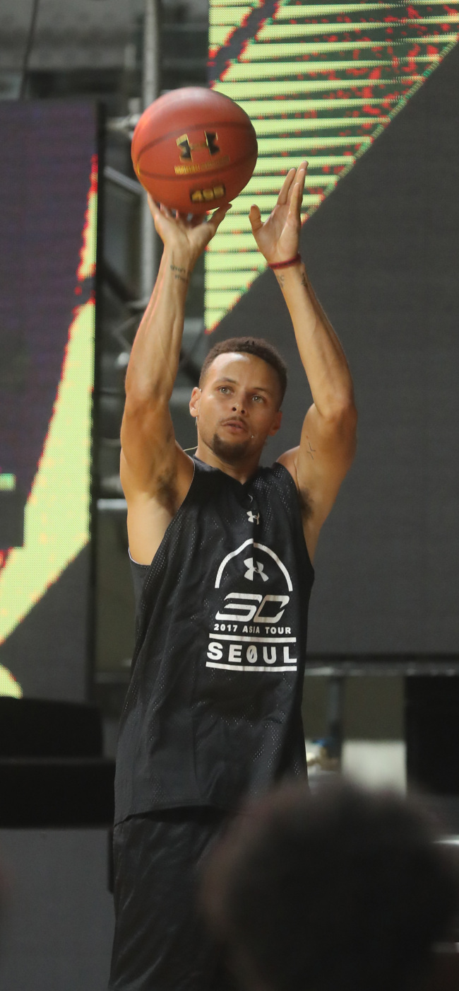 Stephen Curry shoots a three-point shot during a youth basketball clinic at Jangchung Gymnasium in Seoul on Thursday. (Yonhap)