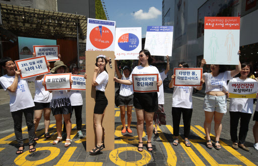 Women's rights activists protest the lack of size-range and biased depiction of women in the Korean fashion industry in Myeong-dong, Seoul, Wednesday. (Yonhap)