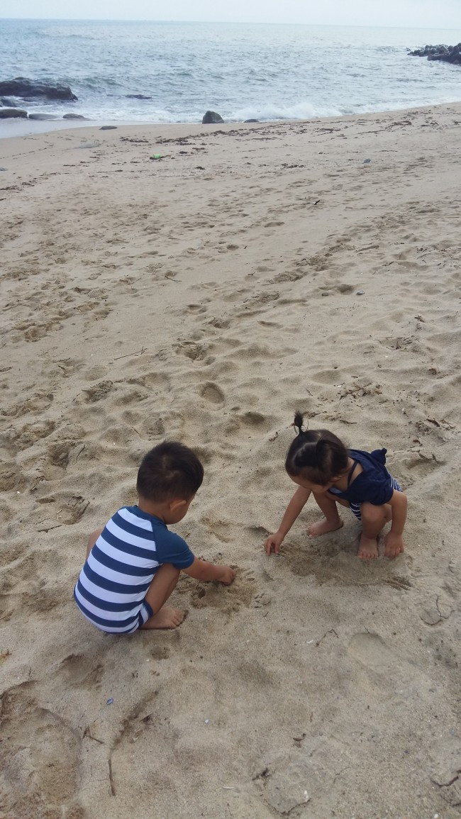 A twin brother and sister play on a beach. (Lee Dong-hoon)