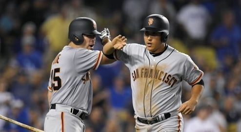 In this Associated Press photo taken on July 28, 2017, Hwang Jae-gyun of the San Francisco Giants (R) is congratulated by Matt Moore after scoring a run against the Los Angeles Dodgers in the teams` Major League Baseball game at Dodger Stadium in Los Angeles. (Yonhap)