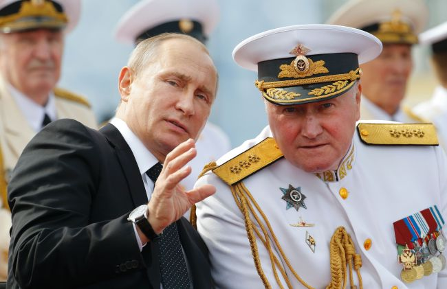 Russian President Vladimir Putin (left) chats with commander in chief of the Russian Navy Admiral Vladimir Korolev as they attend the military parade for Russia`s Navy Day in Saint Petersburg on Sunday. AFP-Yonhap