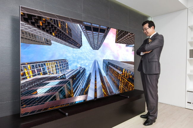 A consumer takes a look at an 88-inch QLED TV displayed at an outlet in Siheung, Gyeonggi Province. (Samsung Electronics)