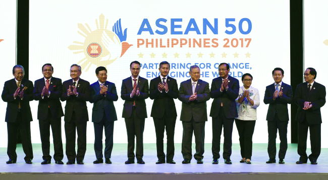 ASEAN Foreign Ministers applaud at the opening ceremony of the 50th ASEAN Foreign Ministers Meeting at the Philippine International Convention Center Saturday, Aug. 5, 2017 in suburban Pasay city, south of Manila, Philippines. They are, from left, Malaysia's Anifah Aman, Myanmar's U Kyaw Tin, Thailand's Don Pramudwinai, Vietnam's Pham Binh Minh, Philippines' Alan Peter Cayetano, Singapore's Vivian Balakrishnan, Brunei's Lim Jock Seng, Cambodia's Prak Sokhonn, Indonesia's Retno Marsudi, Laos' Saleumxay Kommasith and ASEAN Secretary-General Le Luong Minh. (AP Photo/Mohd Rasfan)