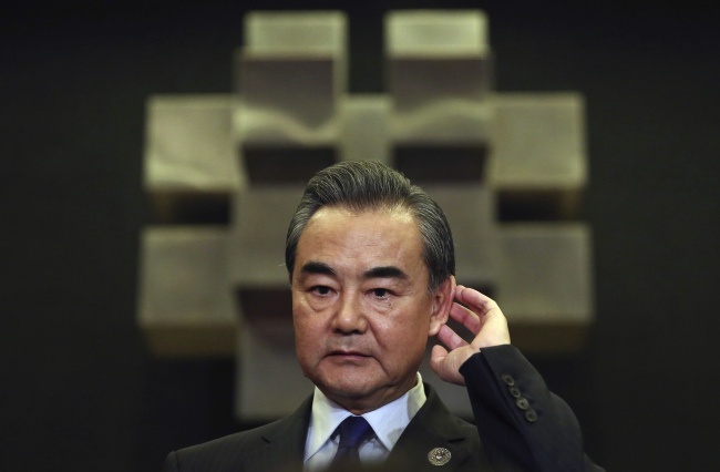Chinese Foreign Minister Wang Yi gestures as he answers questions from reporters as he attends the 50th ASEAN Foreign Ministers' Meeting and its dialogue partners in Manila, Philippines, Sunday, Aug. 6, 2017. Disagreements over North Korea's intercontinental ballistic missile tests and territorial disputes in the South China Sea prevented the region's foreign ministers from promptly issuing their joint communique after an annual gathering in Manila, two Southeast Asian diplomats said Sunday. (AP Photo/Aaron Favila)