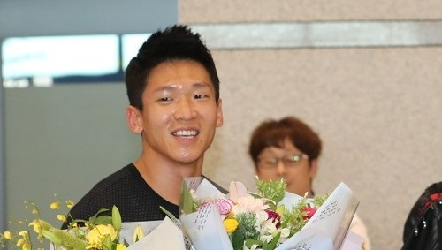 South Korean sprinter Kim Kuk-young receives flowers as he arrives at Incheon International Airport in Incheon on Aug. 7, 2017, after competing at the IAAF World Championships in London. (Yonhap)