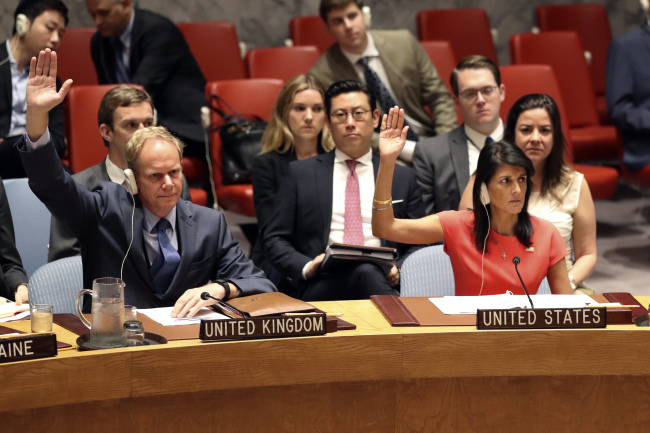 British Ambassador to the United Nations Matthew Rycroft (left) and US Ambassador Nikki Haley vote during a meeting on new sanctions on North Korea in Manila on Saturday. AP-Yonhap