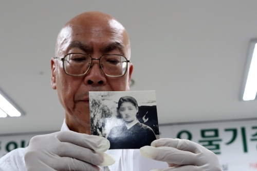 Jikai Taketomi, vice head of the War Archives on Soldiers and Ordinary People in the southwestern Japanese prefecture of Fukuoka, shows a photo of a Korean woman victimized by Japan's wartime sexual slavery during a ceremony at the National Memorial Museum of Forced Mobilization under Japanese Occupation in the largest port city of Busan on Tuesday. (Yonhap)