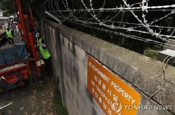 Officials from the Seoul Metropolitan Government and survey experts extract soil and water from an fenced-off area just outside the US military base in Yongsan, on Aug. 9, 2017, as part of its own analysis on possible chemical contamination. (Yonhap)