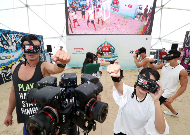 Models demonstrate a merged reality sports game HADO at 5G Land, KT's fifth-generation marketing venue in Haeundae, Busan on Friday. (KT)