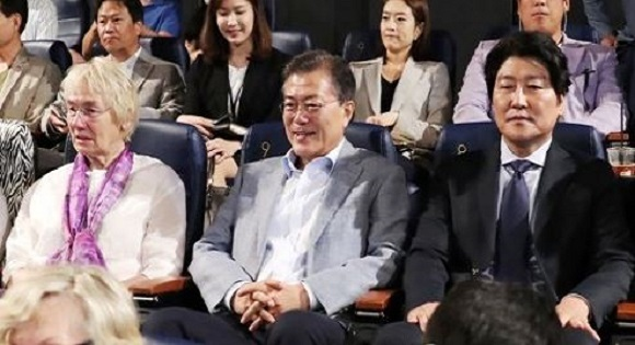 President Moon Jae-in (C) flanked by Edeltraut Brahmstaedt (L) and actor Song Kang-ho watch the movie