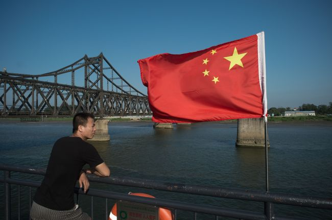 This file picture taken on July 6, 2017 shows a tourist looking out from the Broken Bridge next to the Friendship bridge on the Yalu River connecting the North Korean town of Sinuiju and the Chinese border city of Dandong. (AFP via Yonhap)