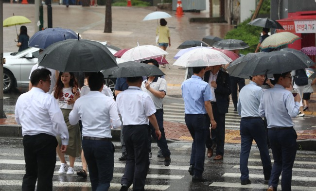 South Korean office workers cross a road in rainy Seoul. (photo credit: Yonhap)