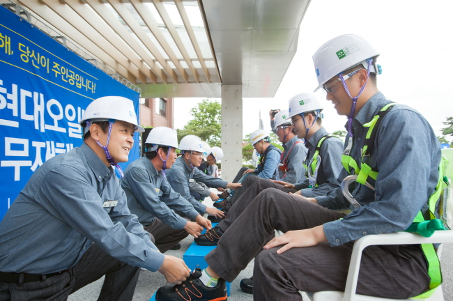 Hyundai Oilbank CEO Moon Jong-bak (left) helps a worker put on safety boots during an event held at Daesan Plant on Wednesday. (Hyundai Oilbank)