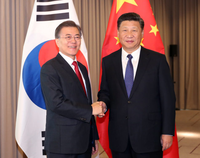 President Moon Jae-in (left) and his Chinese counterpart Xi Jinping shake hands before their summit in Berlin on July 6. (Yonhap)