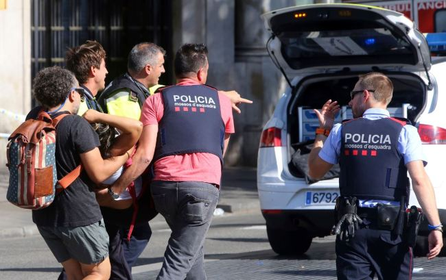 An injured person is carried in Barcelona, Spain, Thursday, after a white van jumped the sidewalk in the historic Las Ramblas district. (AP-Yonhap)