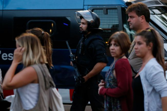 People are escorted by Spanish policemen outside a cordoned off area after a van ploughed into the crowd, killing 13 persons and injuring over 80 on the Rambla in Barcelona on Thursday. (AFP-Yonhap)