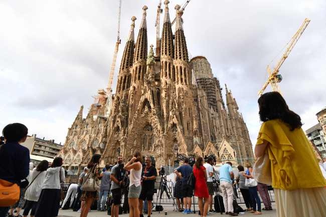 People look at the Sagrada Familia basilica in Barcelona on August 20, 2017, before a mass to commemorate victims of two devastating terror attacks in Barcelona and Cambrils. (AFP-Yonhap)