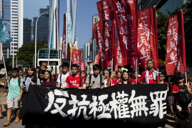 Students lead Hong Kong people with a Chinese banner that reads 'Protesting Authoritarianism is not a Crime' as they march through the streets. (EPA-Yonhap)