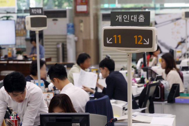 Borrowers talk to consultants about credit-based loans at a bank branch in Seoul on Monday. (Yonhap)
