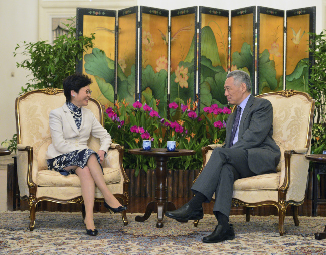 Hong Kong Chief Executive Carrie Lam (left) chats with Singapore Prime Minister Lee Hsien Loong during a call at the Istana presidential palace on Thursday, Aug. 3, 2017 in Singapore. (Roslan Rahman/Pool Photo via AP)