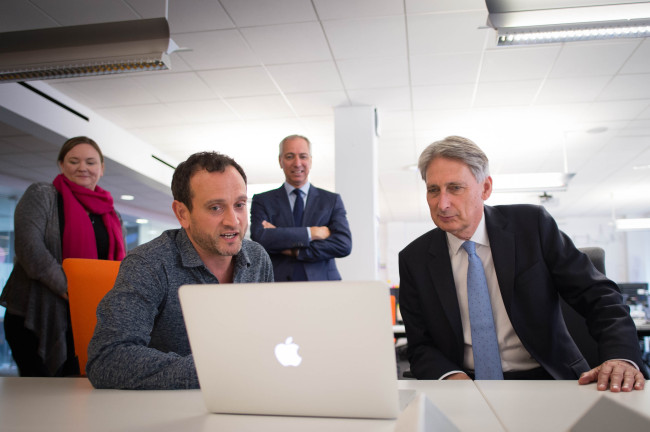 Britain's Chancellor of the Exchequer Philip Hammond (right) meets staff as he tours the IBM office in London on July 26, 2017, as the preliminary estimates for 2017 Q2 GDP are published. Britain's economy advanced slightly in the second quarter, pulled higher by the key services sector despite high inflation and uncertainty over Brexit, according to official data. Gross domestic product grew by 0.3 percent between April and June, a slight increase compared with the first quarter of the year, the Office for National Statistics said in a statement. (AFP PHOTO / POOL)