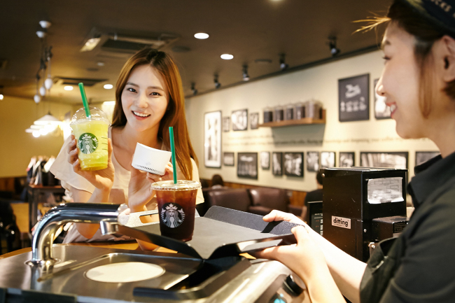 A model demonstrates how to order a drink with the artificial intelligence speaker Nugu at a Starbucks shop in Seoul. (SK Telecom)