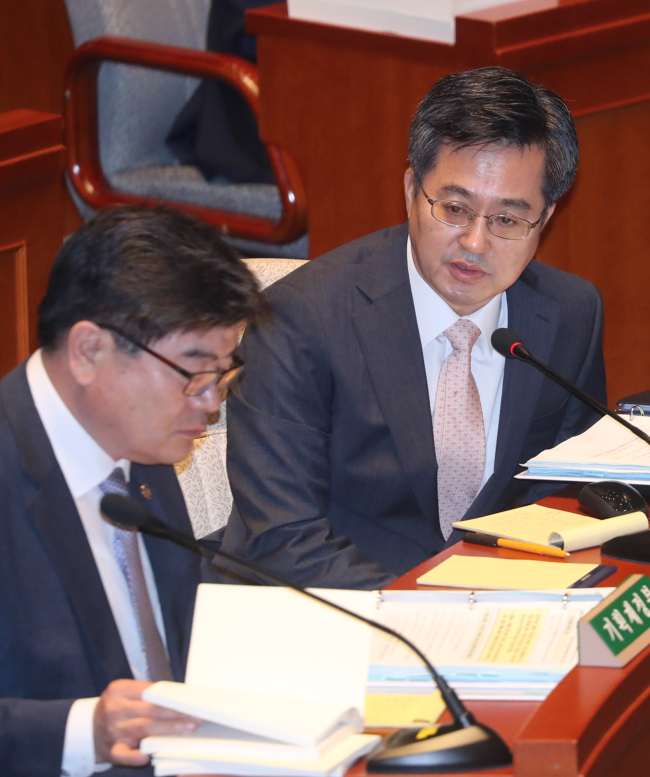 Deputy Prime Minister for Economic Affairs and Finance Minister Kim Dong-yeon (right) sits in a parliamentary budget committee meeting Tuesday. (Yonhap)