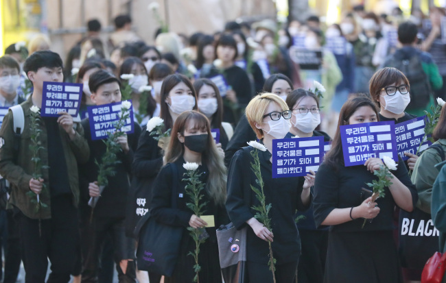 Mourners march in tribute to the 23-year-old victim killed at a uni-sex public bathroom near Gangman Station last year during a memorial event held in Gangnam, southern Seoul, in May.(Yonhap)