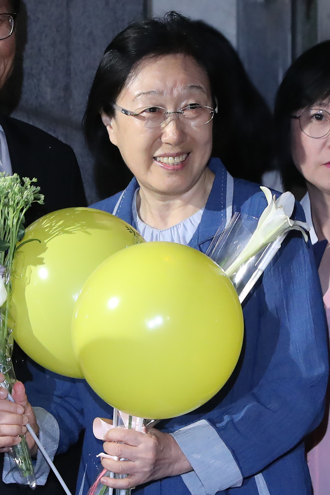 Han Myeong-sook (center) is greeted by supporters and fellow liberal politicians upon her release from a prison in Uijeongbu, Gyeonggi Province, Wednesday. (Yonhap)
