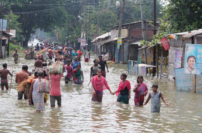 Indian residents wade through flood waters in Balurghat in West Bengal on August 17, 2017. (AFP-Yonhap)