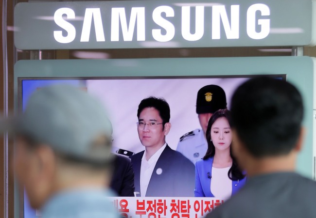 People watch a TV screen showing Samsung Electronics vice chairman Lee Jae-yong's arrival for his verdict hearing at the Seoul Central District Court, Aug. 25, 2017. (Photo credit: Yonhap)