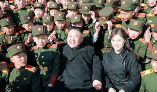 This photo, released by the North`s Korean Central Television on March 3, 2017, shows North Korean leader Kim Jong-un and his wife Ri Sol-ju meeting students of the Red Flag Mangyongdae Revolutionary School in Pyongyang. (Yonhap)