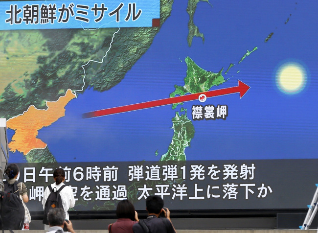 People walk by a TV news program reporting North Korea's missile launch, in Tokyo, Tuesday. (AP-Yonhap)