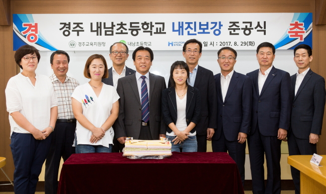 Hyundai Steel staff and executives including Executive Director Ham Young-chul (fourth from right) and the Principal of Naenam Elementary School Kim Nak-gon (fifth from left) pose for a photo at a ceremony to celebrate the completion of a seismic retrofitting project Tuesday. (Hyundai Steel)