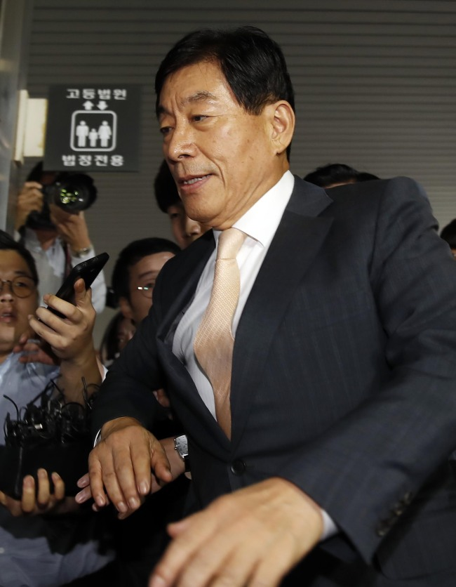 Former intelligence agency chief Won Sei-hoon is escorted to the courtroom at the Seoul High Court to attend his sentencing hearing Wednesday, while being surrounded by reporters. (Yonhap)