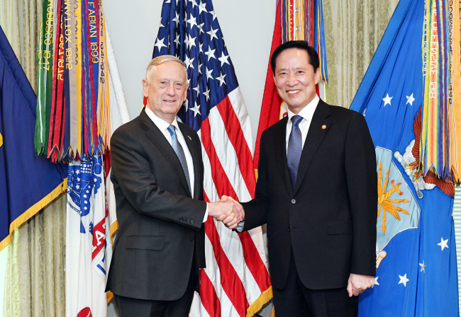 South Korea`s Defense Minister Song Young-moo(right)shakes hands with US Defense Secretary Jim Mattis during thier meeting at the Pentagon. Yonhap