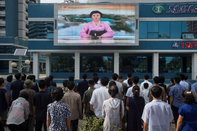 Pyongyang residents watch a video screen showing a newsreader announcing that the country has successfully tested a hydrogen bomb on Sunday. (AFP-Yonhap)