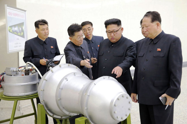 A photograph of Kim Jong-un, center, looking at what they claim was a hydrogen bomb that could be fitted onto a missile. (photo: Korean Central News Agency)
