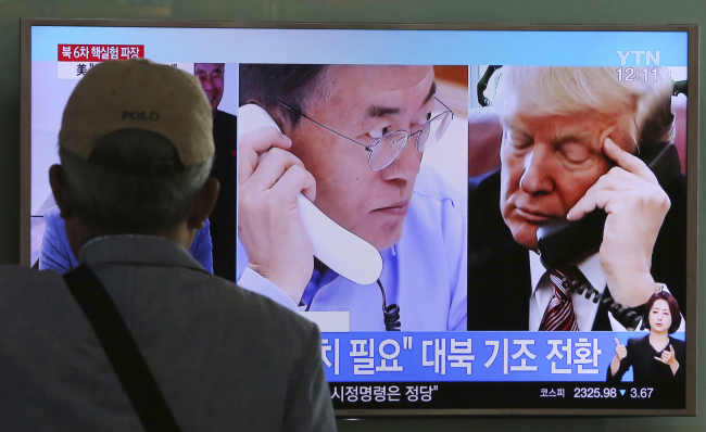 A man watches a television screen showing US President Donald Trump and South Korean President Moon Jae-in during a news program at the Seoul Railway Station in Seoul, Tuesday. (AP-Yonhap)