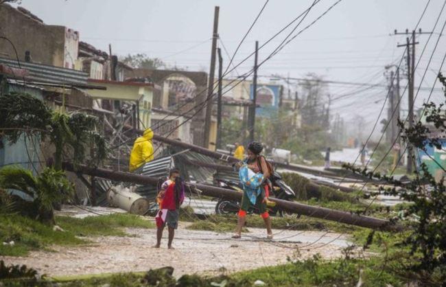 Residents walk near downed power lines felled by Hurricane Irma, in Caribarien, Cuba, Saturday, Sept.9, 2017.(AP)