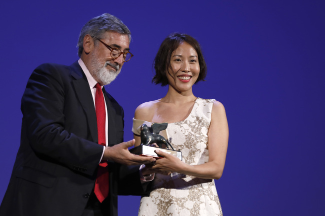 Gina Kim (right) is awarded the prize for best VR story by director John Landis at the 74th Venice Film Festival at Venice Lido in Italy, Saturday. (AP-Yonhap)