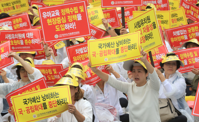 "Members of the Korea Kindergarten Association hold a banner reading ""Equal Support for Public and Private Kindergartens!"" at a rally in Yeouido, western Seoul, Monday. Yonhap"