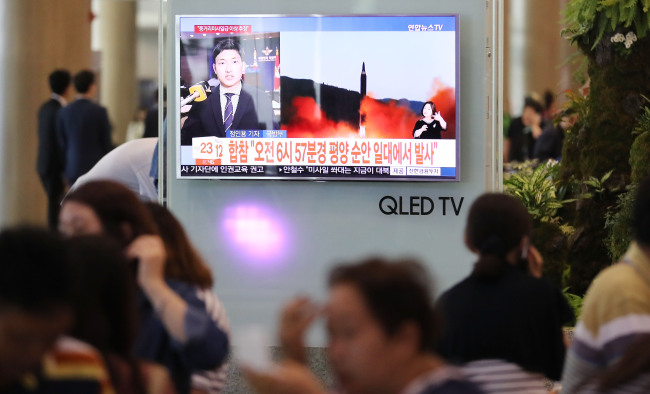 People watch a TV report at Incheon Airport, Friday, after North Korea earlier in the day fired what appeared to be an intermediate-range missile over Japan that flew approximately 3,700 kilometers and fell into the North Pacific Ocean. (Yonhap)