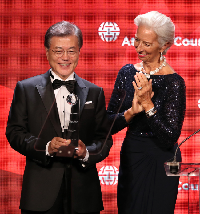 South Korean President Moon Jae-in is presented with the Global Citizen Award by Christine Lagarde, managing director of the International Monetary Fund, in New York on Tuesday. Moon was one of three winners of the annual award given by the US think tank Atlantic Council. (Yonhap)