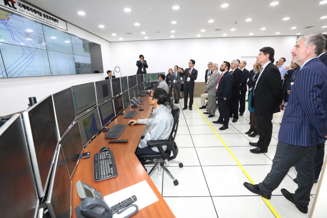 A group of Central and South American ICT ministers and high-ranking government officials are briefed about telecom firm KT's low-latency data transfer systems. (KT)