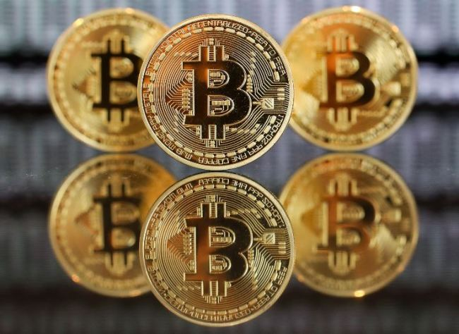 A collection of bitcoin tokens stand in front of an illustration of binary code in this arranged photograph taken in London on Jan. 4. (Bloomberg)