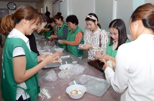 Foreign women learn to make half-moon shaped rice cake ahead of the Chusok holiday in Korea. (Yonhap)