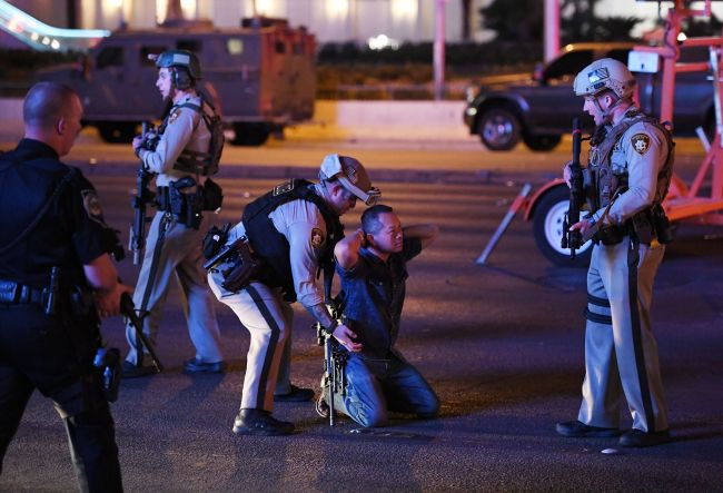 Police officers stop a man who drove down Tropicana Ave. near Las Vegas Boulevard and Tropicana Ave, which had been closed after a mass shooting at a country music festival on Sunday  in Las Vegas, Nevada. (AFP-Yonhap)