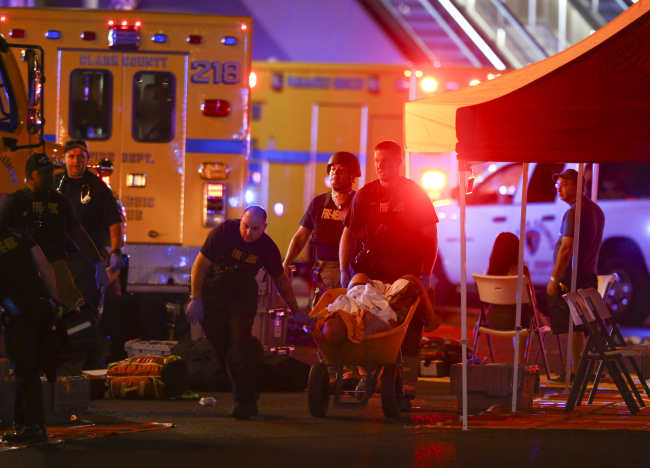 A wounded person is walked in on a wheelbarrow as Las Vegas police respond during an active shooter situation on the Las Vegas Stirp in Las Vegas Sunday.  (AP-Yonhap)