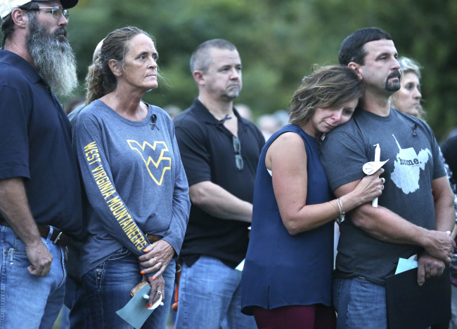 Michelle Potts of Hedgesville, W.Va. leans on the shoulder of her husband, Gary Potts, during a candlelight vigil she organized for her best friend, Las Vegas shooting victim Denise Burditus of Martinsburg, W.Va., Thursday, Oct. 5, 2017 on the football field at Hedgesville High School. Burditus, 50, was one of 58 people murdered at the Route 91 Harvest country music festival in Las Vegas, Nev. Sunday, Oct. 1, 2017. (AP-Yonhap)
